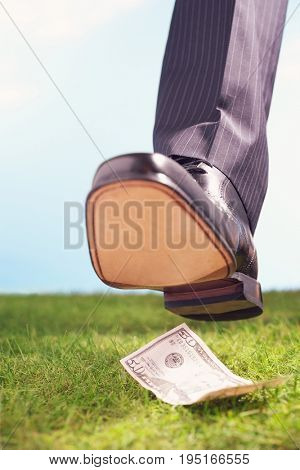 Closeup of a businessman stepping on fifty dollar bill in grass