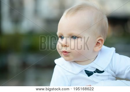 Cute baby boy small little caucasian child with blue eyes and blond hair on sunny summer day outdoors in white shirt on blurred natural background