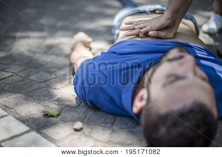 girl making reanimation to an unconscious guy after heart attack