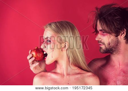 man and woman with creative fashionable makeup on face hold pomegranate fruit on red background beauty and fashion allergy healthcare and vitamin vegetarian and dieting hemoglobin couple in love