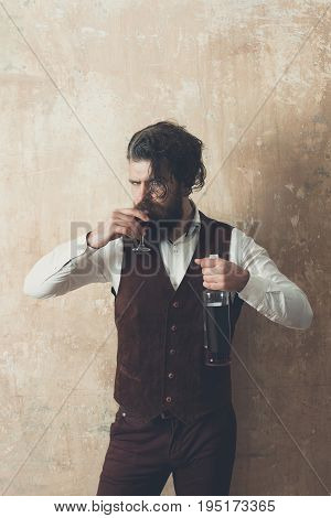 Hipster drinking glass of wine. Bearded man with long beard and messy hair holding bottle on beige wall. Depression. Alcohol abuse and alcoholism. Addictive. Convive. Unhealthy lifestyle. Bad habits