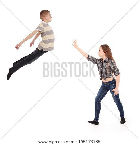 Girl keeps the boy in will in the air. Levitation with the power of thought. Isolated on white