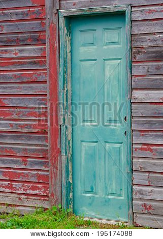 Green, blue door on a red barn