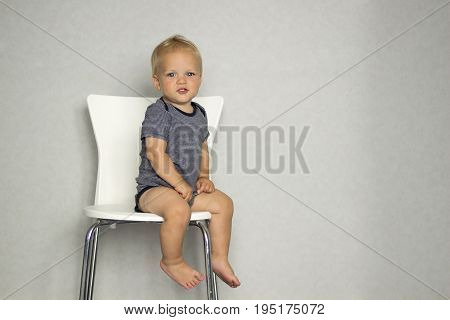 Cute Toddler Sitting On The Chair Against Gray Wall And Looking At Camera. Copy Spase
