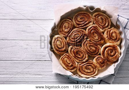 Raw cinnamon rolls in baking pan on kitchen table