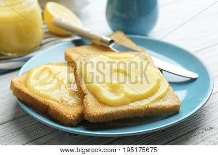 Plate with fresh toasts and delicious lemon curd on wooden table, closeup