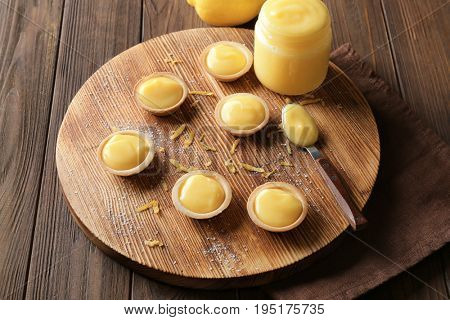 Composition with tasty cookies and lemon curd on wooden table
