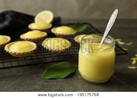 Glass jar with lemon curd and tasty cookies on table