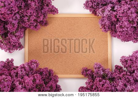 Frame with wood and purple lilac flowers On the sides white background in the center