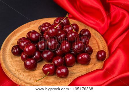 Large red dark cherries on a wooden stand with red cloth