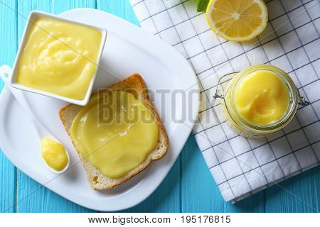 Composition with fresh toast and delicious lemon curd on wooden table