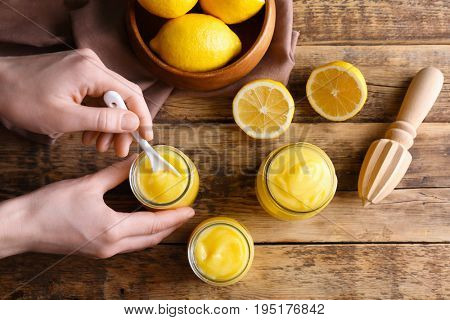 Woman taking lemon curd from glass jar on wooden background