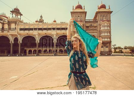 Beautiful happy woman with headscarf, dancing around building with towers of the royal Palace of Mysore, Karnataka state, India