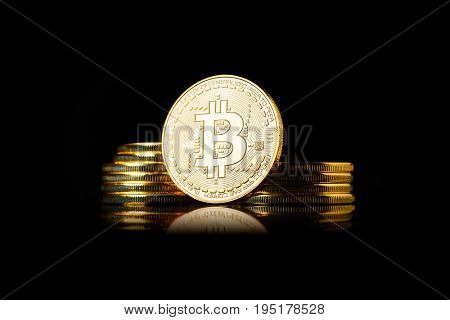 Stack of golden Bitcoin coins on a black background