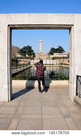 January 2 2015. Nanjing China. A chinese man taking pictures of chinese visitors at the revolutionary martyrs Memorial Yuhuatai park in Nanjing China on a sunny day in Jiangsu province.