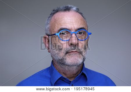 man with glasses and blue shirt on grey background