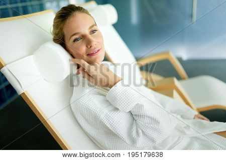 Portrait of attractive woman relaxing in spa center wearing bathrobe