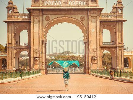 Lady with headscarf going to the indian landmark - Historical gates in Indo-Saracenic style. Old Royal Palace of Mysore in Karnataka, India