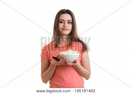 cute young woman with pop-corn watching a tv isolated on white background