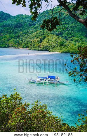 Beautiful view of a tropical island Snake with white traditional banca boat full tourists. El Nido, Palawan, Philippines.