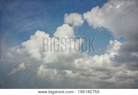 Blue sky with gathering cumulus clouds in shades of blue ranging from turqouise to cobalt blue vintage light grunge texture. Good for backgrounds.