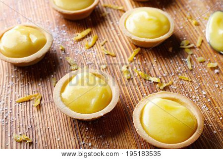 Tasty cookies with lemon curd on wooden table