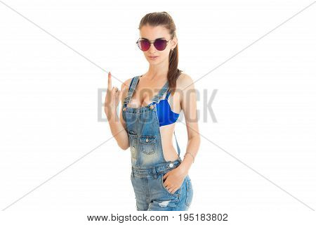 beautiful young girl in jeans overall and blue bra with big round silicon breasts posing on camera isolated on white background