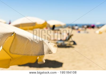 closeup of some beige umbrellas and in a beach in the Mediterranean sea, with many unrecognizable people sunbathing in the background