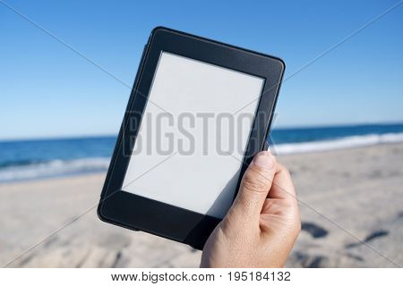 closeup of the hand of a young caucasian man on the beach holding a tablet or e-reader with a white blank space in its screen