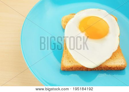 Plate with delicious sunny side up egg and toast, closeup