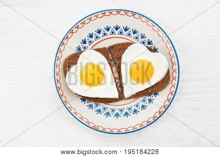 Plate with delicious sunny side up eggs and bread slices on wooden background
