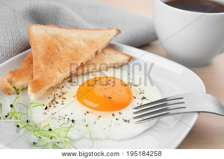 Plate of homemade over easy fried egg with toasts and cup of tea on table
