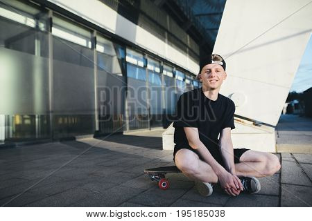 A smiling teenager skater sits on a blackboard on the background of modern architecture. A skater resting on a board for skiing.