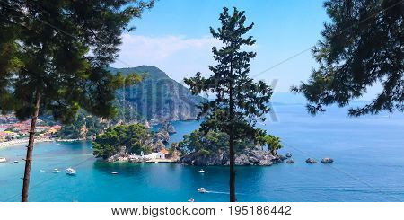 Summer greek vacation panoramic background with turquoise sea water bay, boats and pine trees in Parga, Greece