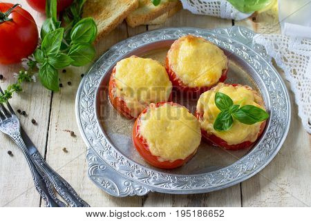 Stuffed Tomatoes. Tomatoes Baked With Cheese And Chicken On A Wooden Kitchen Table.