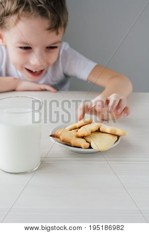 A Child Steals From A Plate Of Freshly Baked Homemade Cookies