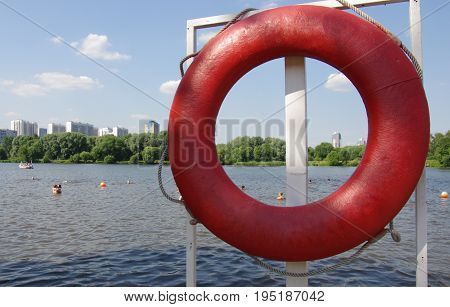 Red lifebuoy on the shore of the lake