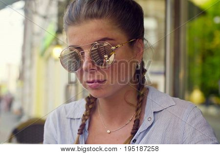 Close up portrait of young woman in sunglasses against cityscape