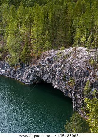 Marble quarry in Ruskeala Park in Republic of Karelia, Russia. Ruskeala - tourist center, located on the ground filled with groundwater former marble quarry. In the foreground is the grotto.