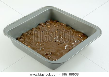 Raw brownie or chocolate cake batter with caramel chips and dried cranberries in baking pan on white wooden table