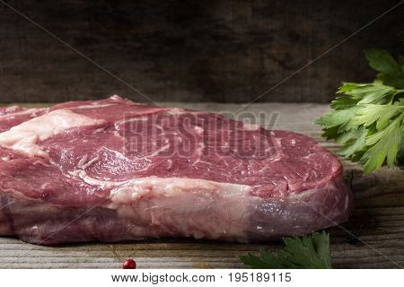 Raw Rib Eye Steak with parsley on wooden rustic background