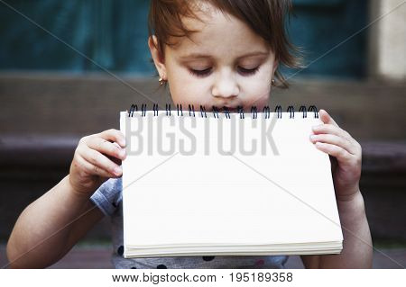 Cute little child girl holding notebook with clean papers for work and study. Place to insert text or photos.