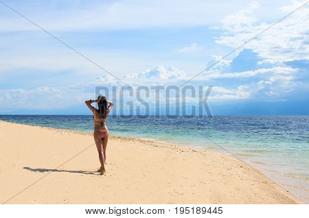 Beautiful girl on beach. Summer beach photo. Woman on vacation. Young girl in bikini under sunlight. Tropical island paradise holiday travel. White sand beach and blue seawater. Perfect beach view