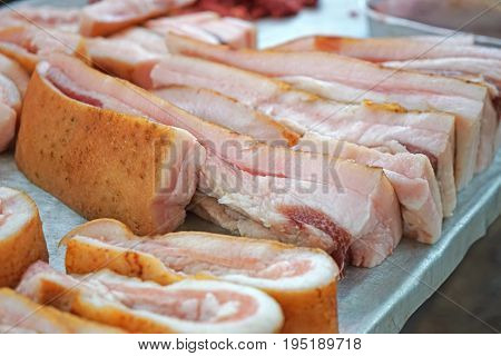 Fresh raw pork pieces on counter in market