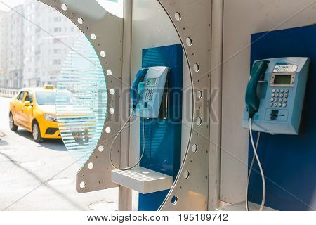Street payphone with yellow taxi in the background. Travel concept, passenger transportation, communication.