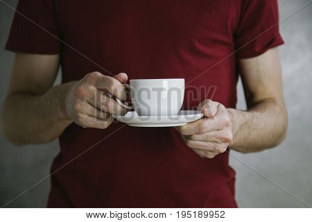 Man in red t-shirt holding white coffee cup.Mock up of clean coffee cup.Horizontal mockup.