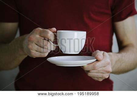 Young man in red t-shirt holding white cup in hands. White mug for man, gift. Mockup for designs.