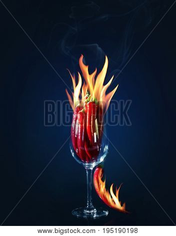 Burning chili peppers and glass on dark background