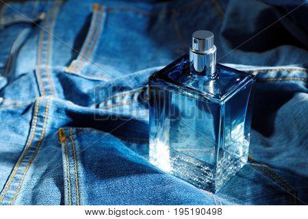 Bottle of modern male perfume on denim background