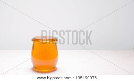 A jar of honey filled to the brim with copy space to the right. Life is full and sweet!